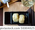 Fresh Japanese triangular onigiri with rice at black plate 56904025