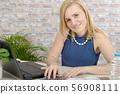 beautiful young blonde woman using laptop 56908111