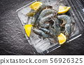 raw shrimps on ice with spices lemon on the dark 56926325