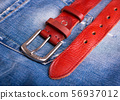 A belt lying on denim. Fashionable red belt 56937012