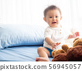 Portrait happy baby boy is sitting on the bed in the room. 56945057