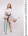 Happy woman with broken leg in bandage standing on 56950621