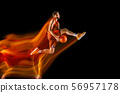 Young caucasian basketball player against dark background in mixed light 56957178