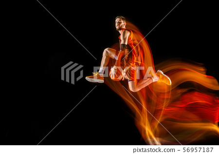 Young caucasian basketball player against dark background in mixed light 56957187
