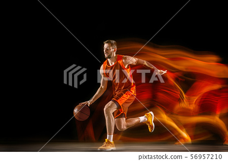 Young caucasian basketball player against dark background in mixed light 56957210
