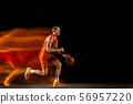 Young caucasian basketball player against dark background in mixed light 56957220