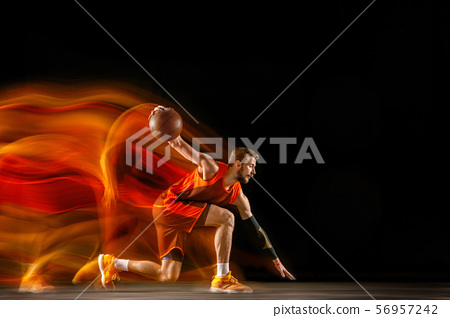 Young caucasian basketball player against dark background in mixed light 56957242