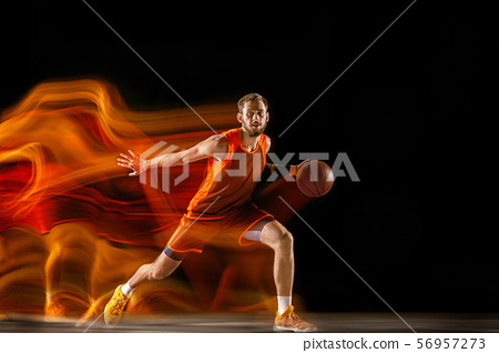 Young caucasian basketball player against dark background in mixed light 56957273
