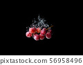 Red grapes sinking in water on black background 56958496