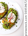Poached eggs with avocado guacomole on brown bread with sesame seeds. Healthy breakfast on a white 56959672