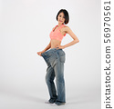 sporty fitness woman in loose jeans after losing weight on white background. healthy sport 56970561