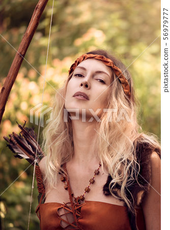 Beautiful girl archer with long blond hair with a 56979777