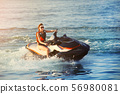 Young adult sporty caucasian woman riding jet ski 56980081