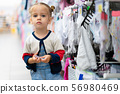 A little Caucasian girl is standing near a shop 56980469