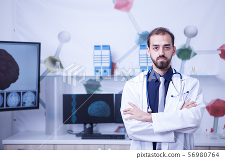 Handsome young doctor with arms crossedin his cabinet at the hospital1 56980764