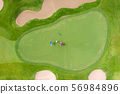Aerial view of players on a green golf course. 56984896