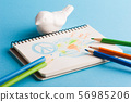 Notepad with color pencils and child drawing 56985206