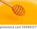 Close up wooden dipper in honey bowl 56988357