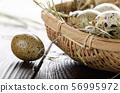 Fresh organic quail eggs in small wicker basket on 56995972