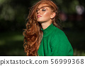 Sunshine young smiling woman with red curly hair is wearing green sweater in autumn park. 56999368