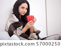 Sick woman in bed with thermometer is having high temperature fever 57000250