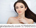 Spa. Young beautiful woman lying on the bed with happy spa body and scrub skin at spa salon. concept 57000503