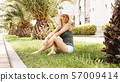 Woman in hat under palm trees relaxing. Summer vacation or holiday. 57009414