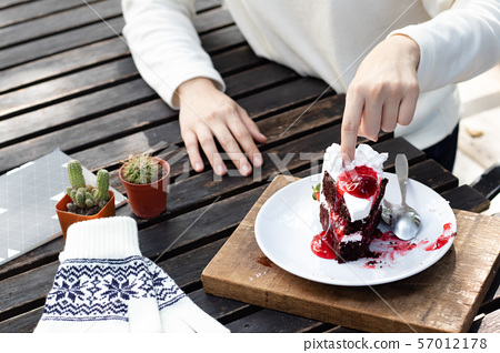Woman hand dipping cream on chocolate cake. 57012178