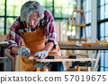 Old Asian craftsman act as measurement of wood 57019675