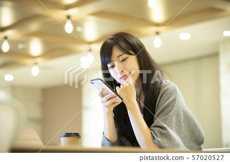 젊은 여성 · 따뜻한 조명 사무실 57020527
