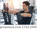 Handsome man lowering weight of fitness machine 57021946
