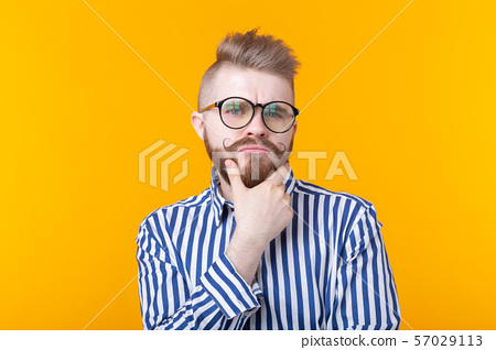 Cute intelligent young man with a beard and with glasses poses on a yellow background and thinks 57029113