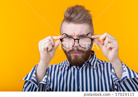 Young handsome guy is looking at his glasses while standing against a yellow background. The concept 57029115