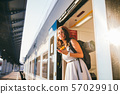 Woman peeking out train. Woman railway station. Young happy woman pulling face out train door 57029910