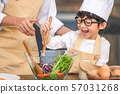 Cute little Asian happy boy interested in cooking 57031268