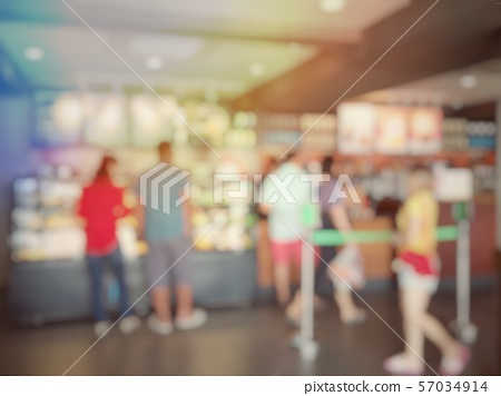 Blurred image of cashier with long line of people 57034914