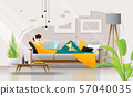 Young man lying on sofa with laptop in living room 57040035