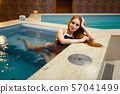 Attractive lady enters the water at the pool 57041499