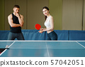 Man teaches a woman to play ping pong 57042051