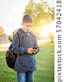 Young Hispanic Boy Walking Outdoors With Backpack 57042418