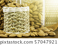 Almonds seeds pour from wood spoon on textured wooden background, top view. 57047921