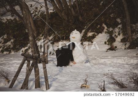 A woman making a snowman 57049692