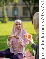 Dark-eyed muslim woman eating pizza with friend 57055751
