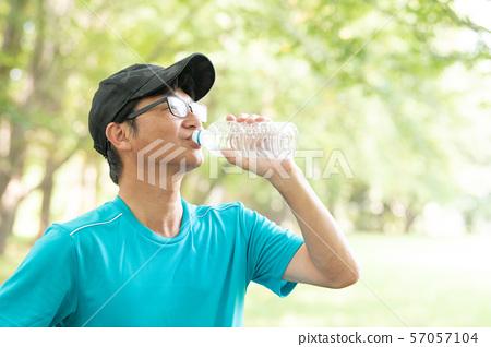 從塑料瓶的日本中年人飲用水 57057104