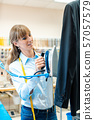 Woman in textile cleaner ironing clothes 57057579
