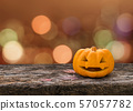 Halloween pumpkin Jack O'Lantern happy face on wood table with orange bokeh background 57057782