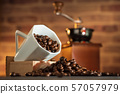 Coffee bean in the white cup and coffee grinder on wooden table. 57057979