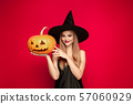 Young woman in hat as a witch on red background 57060929