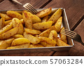 Potato wedges, oven baked, in a baking tray on a dark rustic wooden background, with two forks 57063284