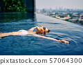 Young woman relaxing in roof top swimming pool and floating in water 57064300